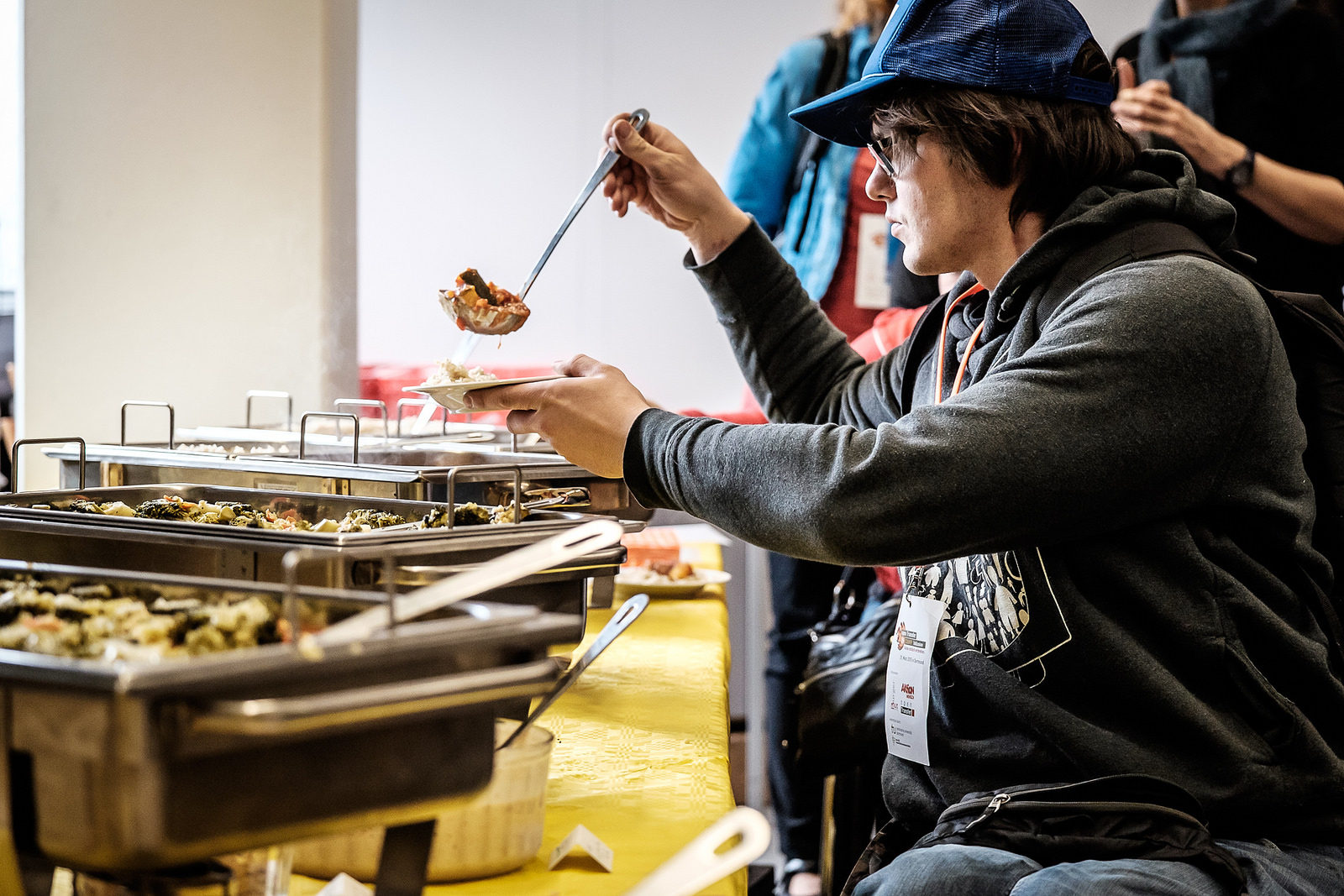 Ein Rollstuhlfahrer nimmt sich selbst das Essen aus den Töpfen des Caterings. Der Tisch ist so tief angebracht, dass er mit dem Löffel im Sitzen gut das Essen schöffeln kann.