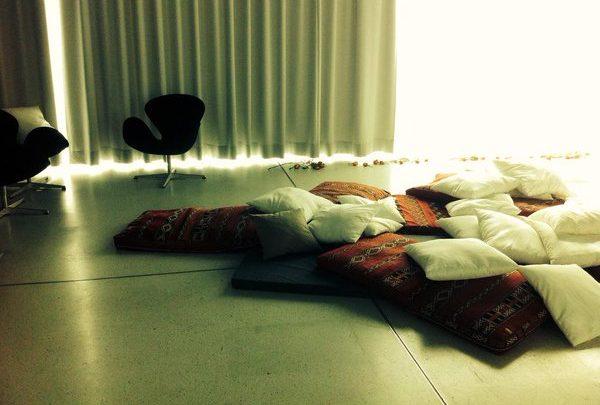 Ein Raum, der durch Vorhänge abgedunkelt werden kann. Im Vordergrund eine schwarze dünne Matratze mit vielen roten und weißen Kissen. Im Hintergrund zwei gemütliche Drehstühle. Unter dem Fenster liegen Rosenblüten.