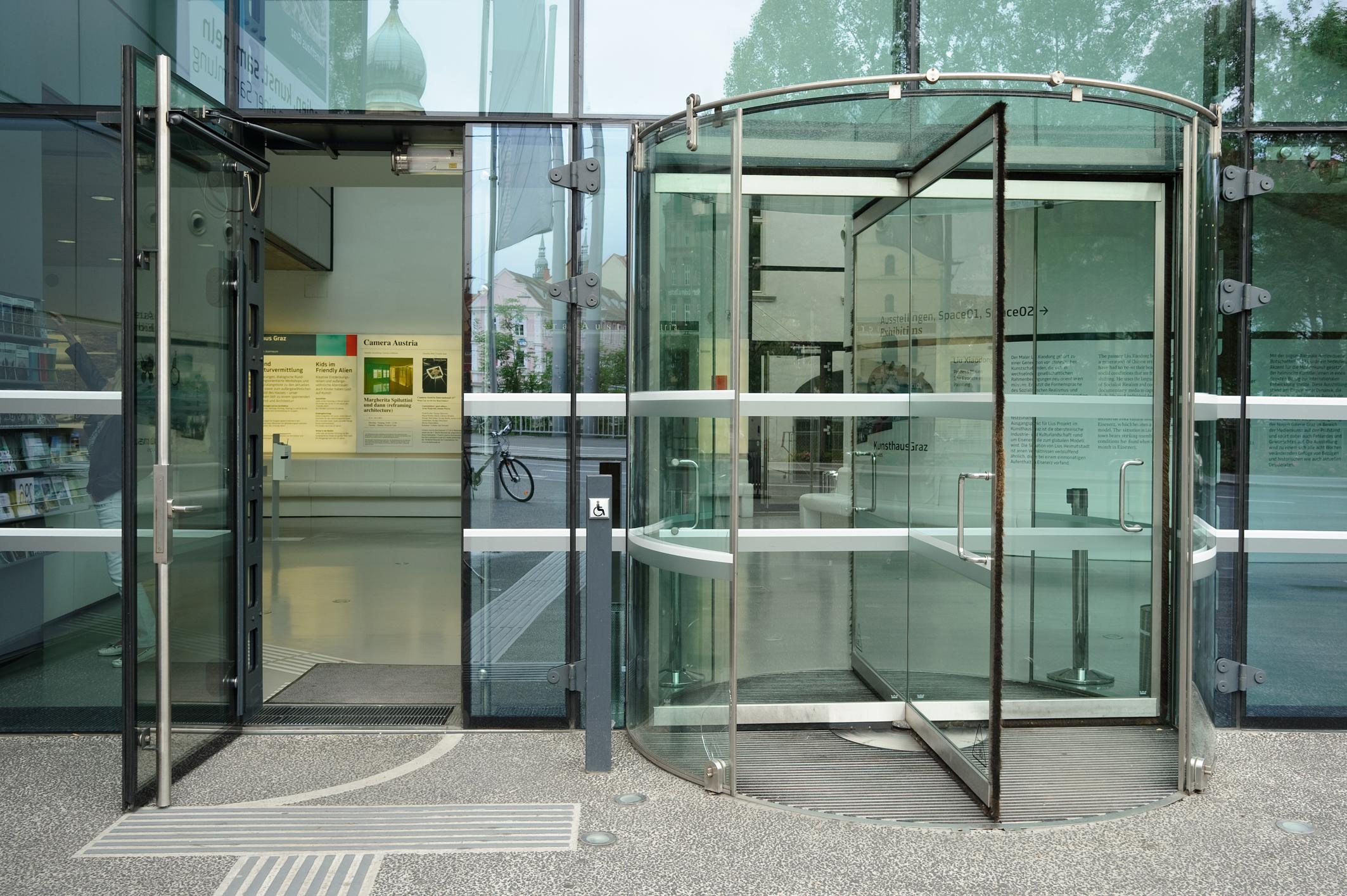 Blick auf den Eingang des Universalmuseums Joanneum in Graz, Österreich. Rechts befindet sich eine Drehtür aus Glas. links ein separater Eingang für Menschen mit Rollstuhl. Ein Knopf zum automatischen Türöffnen ist sichtbar. Auf dem Boden befinden sich taktile Blindenleitsysteme.
