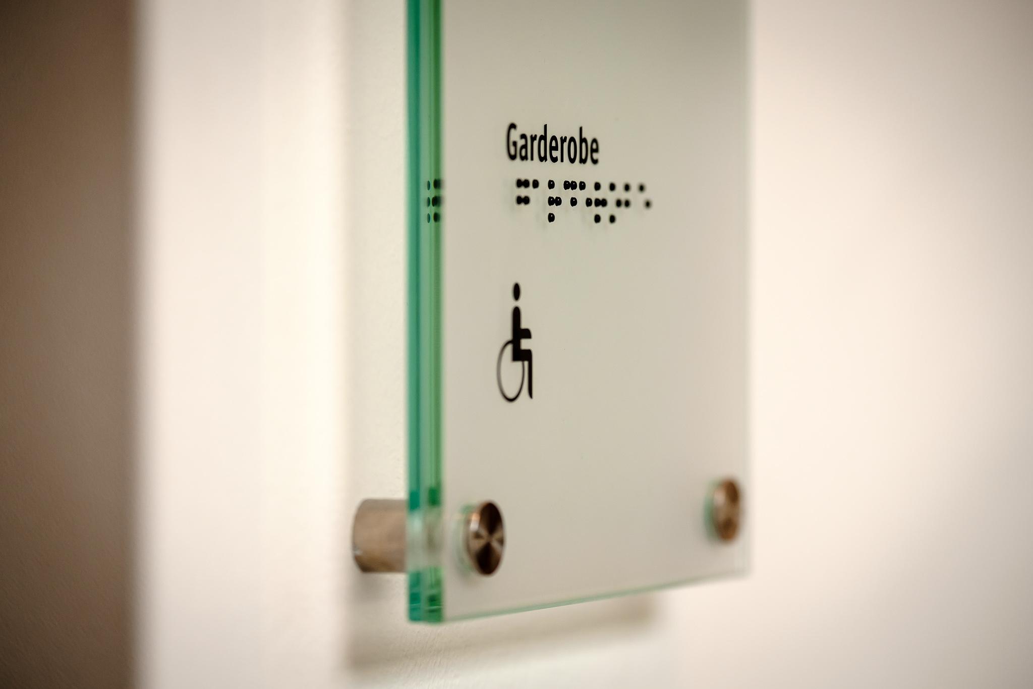 Ein Schild aus Glas mit schwarzer Markierung. Darauf das Rollstuhl-Symbol für die behindertengerechte Toilette und die Überschrift Garderobe. Darunter auch in Braille-Schrift.