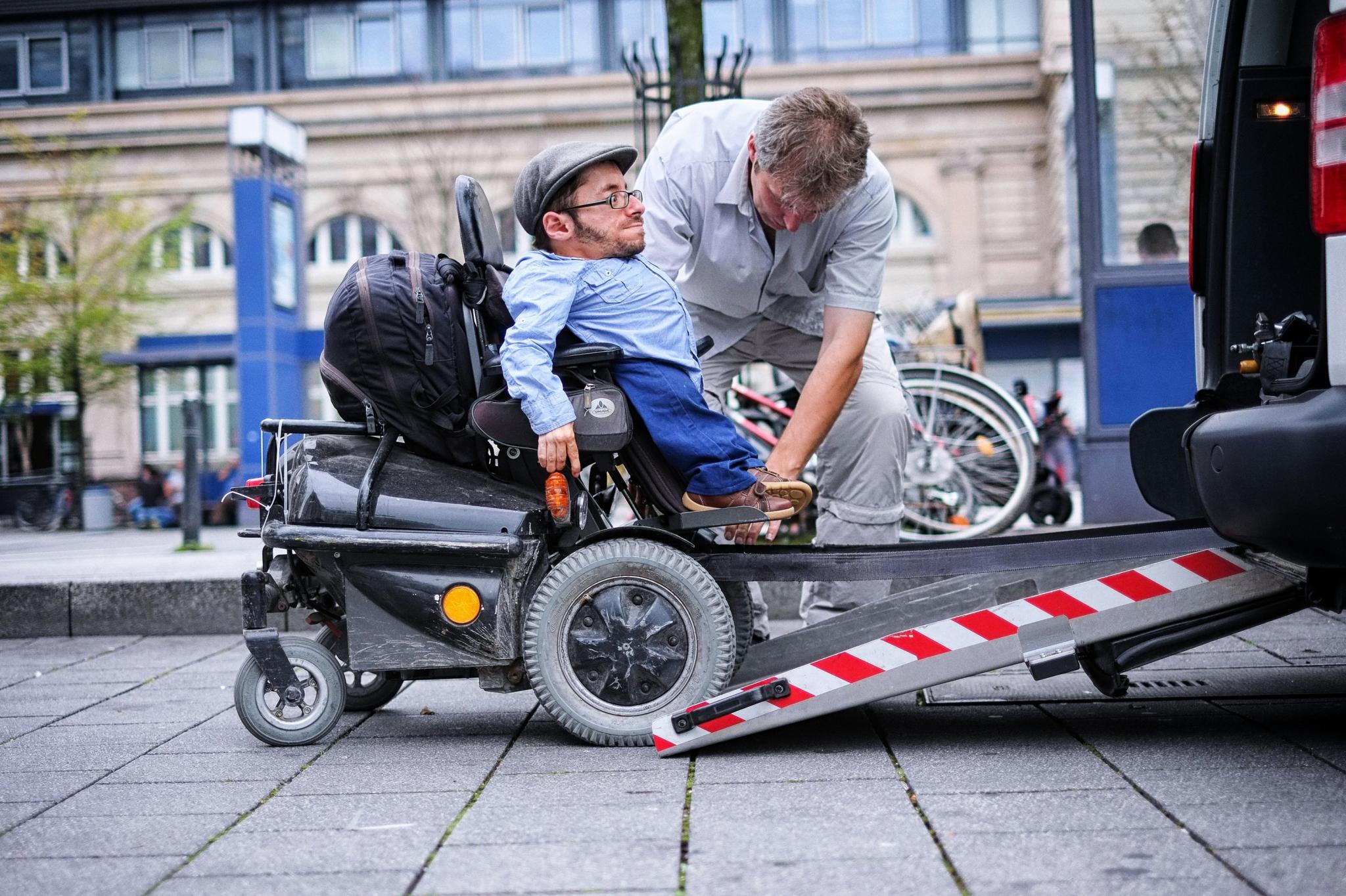 Ein Rollstuhlfahrer gelangt über eine kleine Rampe in das Rollstuhltaxi. Neben ihm steht ein Taxifahrer, der ihm beim Einsteigen hilft.