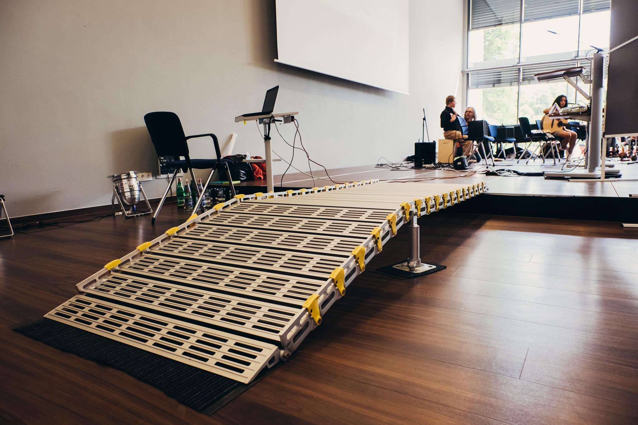 Eine lange Rampe führt auf eine Bühne. Sie ist aus silbernem Metall und hat an den Seiten gelbe Elemente. Im Hintergrund sitzen Podiumsgäste auf Stühlen.