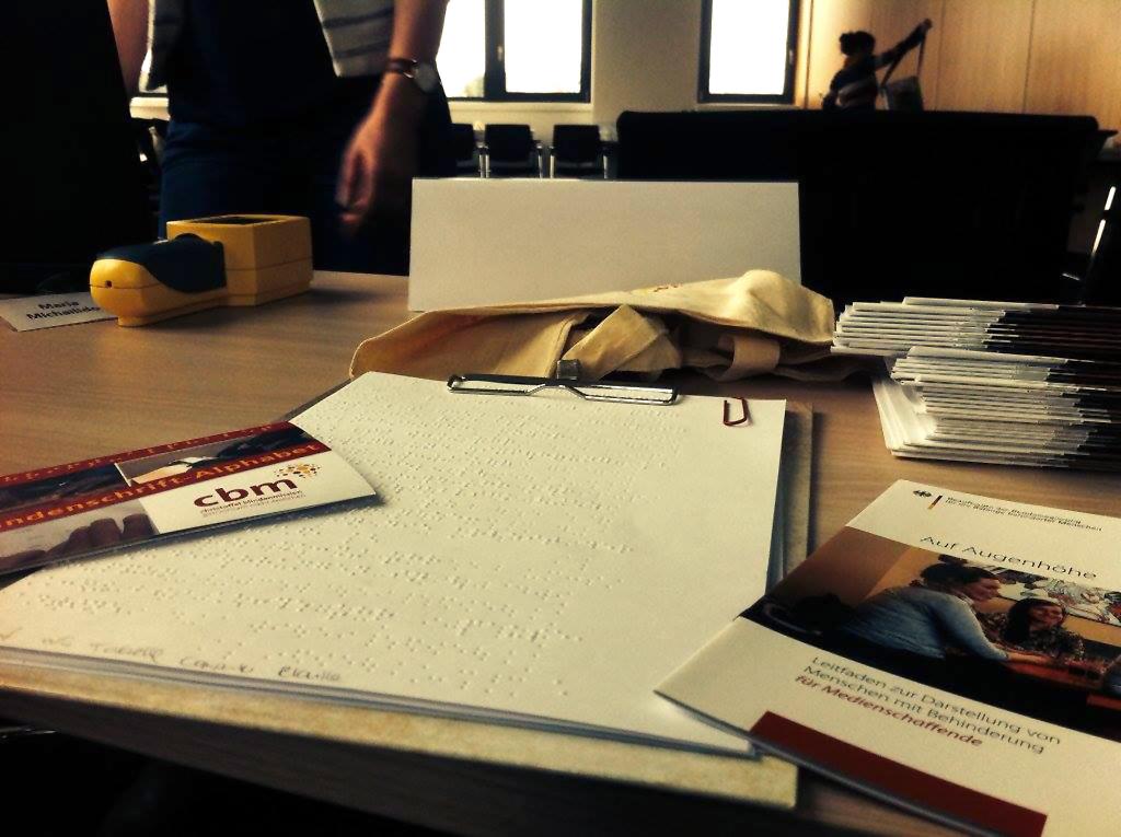 Auf einem Tisch liegen Broschüren. Eine ist in Braille-Schrift geschrieben.