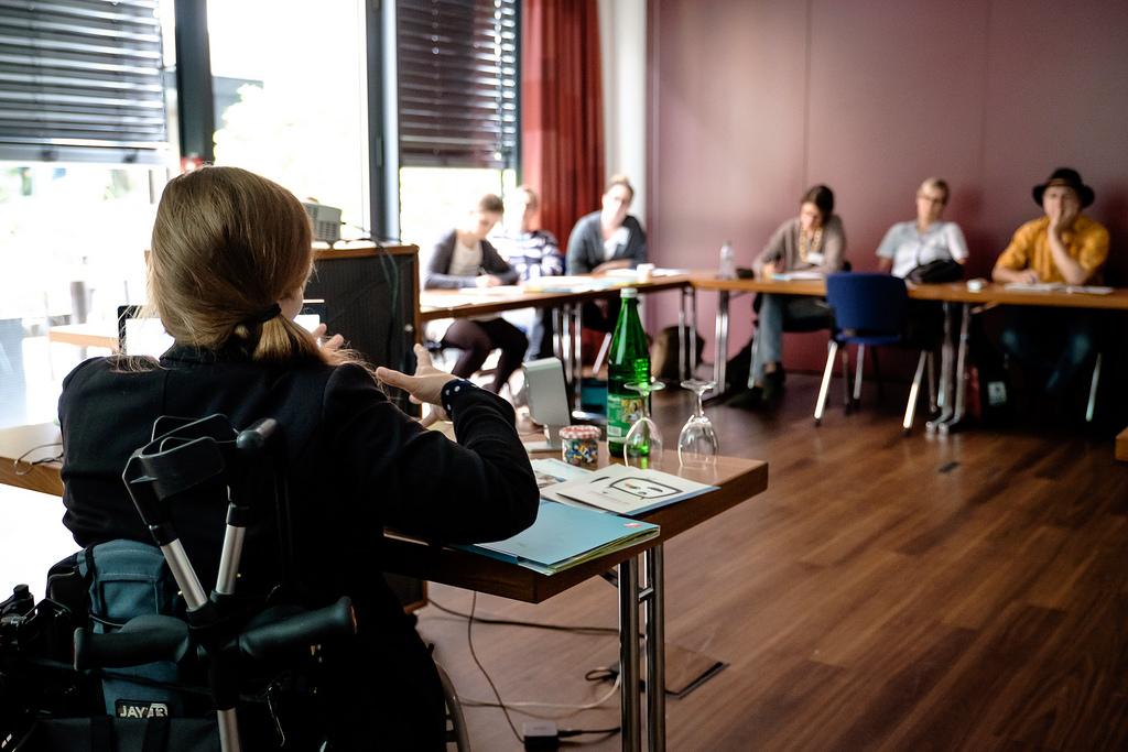 Eine Workshop-Geberin im Rollstuhl gibt einen Workshop. Sie sitzt vor einer Gruppe Menschen, die zuhören und mitschreiben an Tischen vor ihr.