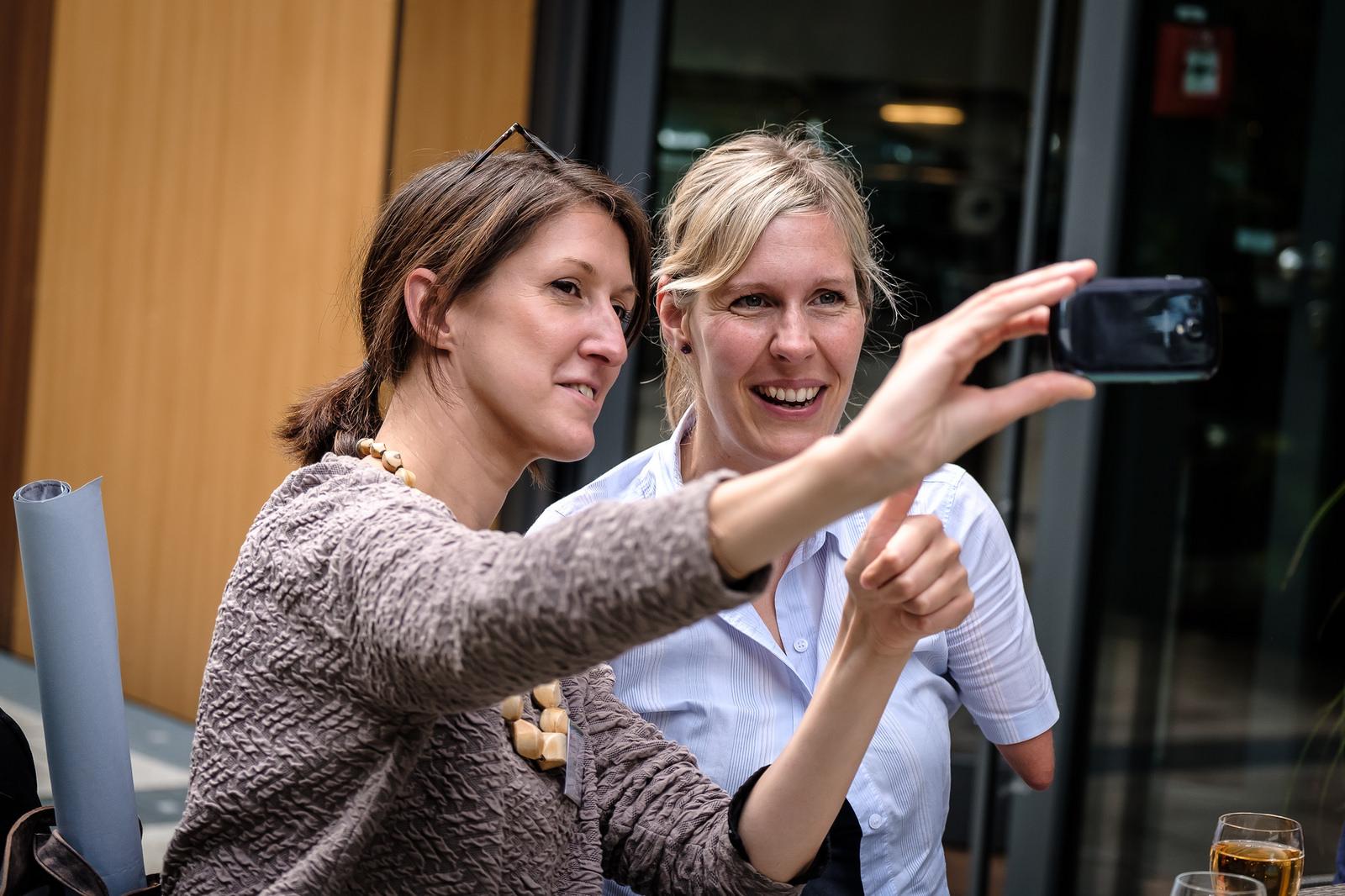 Zwei Frauen machen ein Selfie. Eine der beiden hat eine Behinderung durch verkürzte Arme. Sie lächeln in die Kamera.
