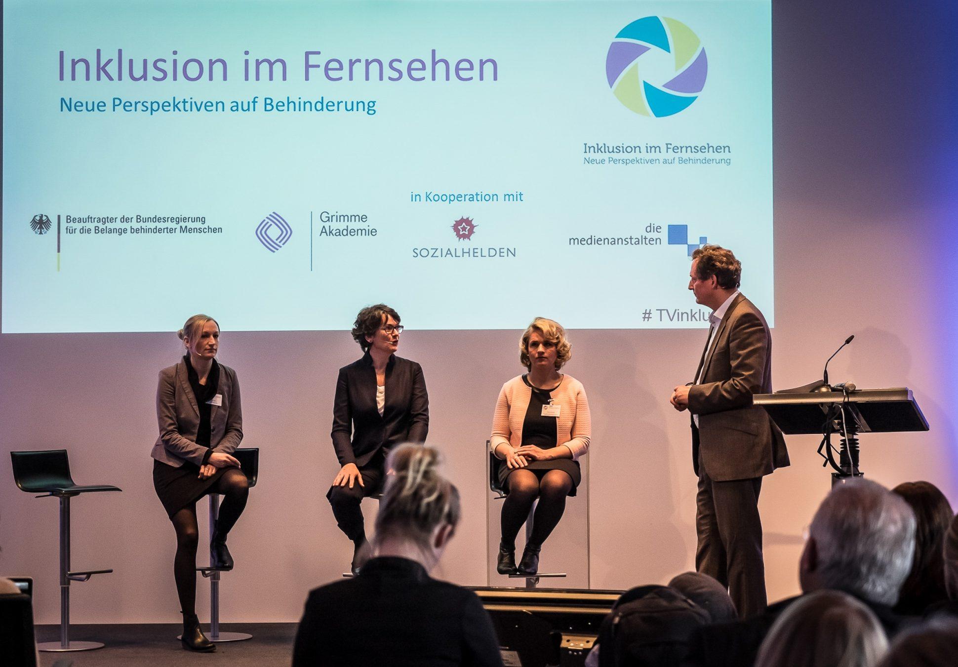 """Ein Podium auf der Veranstaltung """"Inklusion im Fernsehen"""" von der Grimme Akademie bei RTL in Köln. Auf dem Podium sitzen drei Frauen, zwei blonde Frauen und eine dunkelhaarige Frau. Eine der Frauen ist blind. Neben ihnen steht der Moderator."""