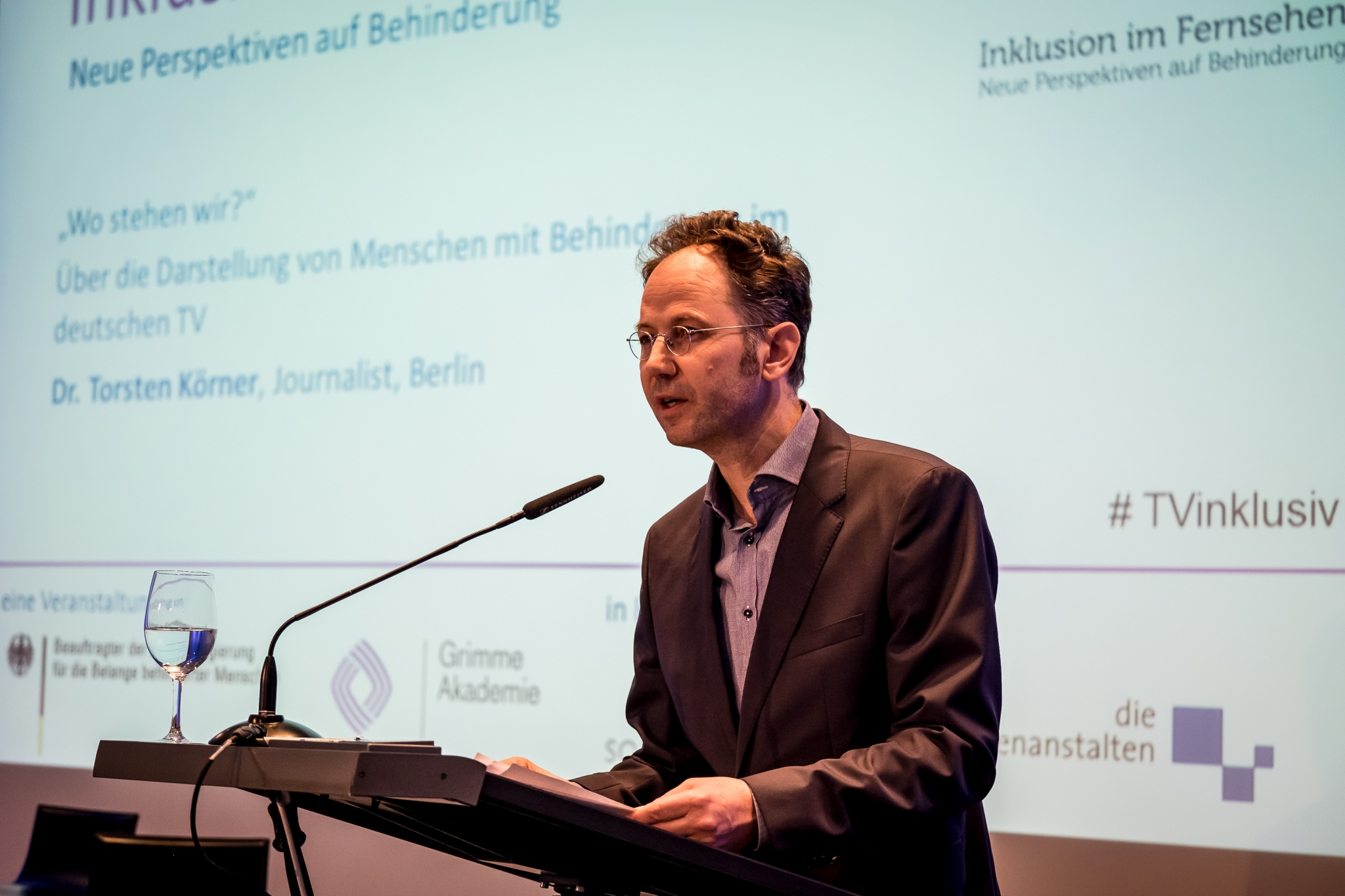 Ein Mann steht am Rednerpult und hält einen Vortrag. Im Hintergrund sind seine Vortragsfolien zu sehen.