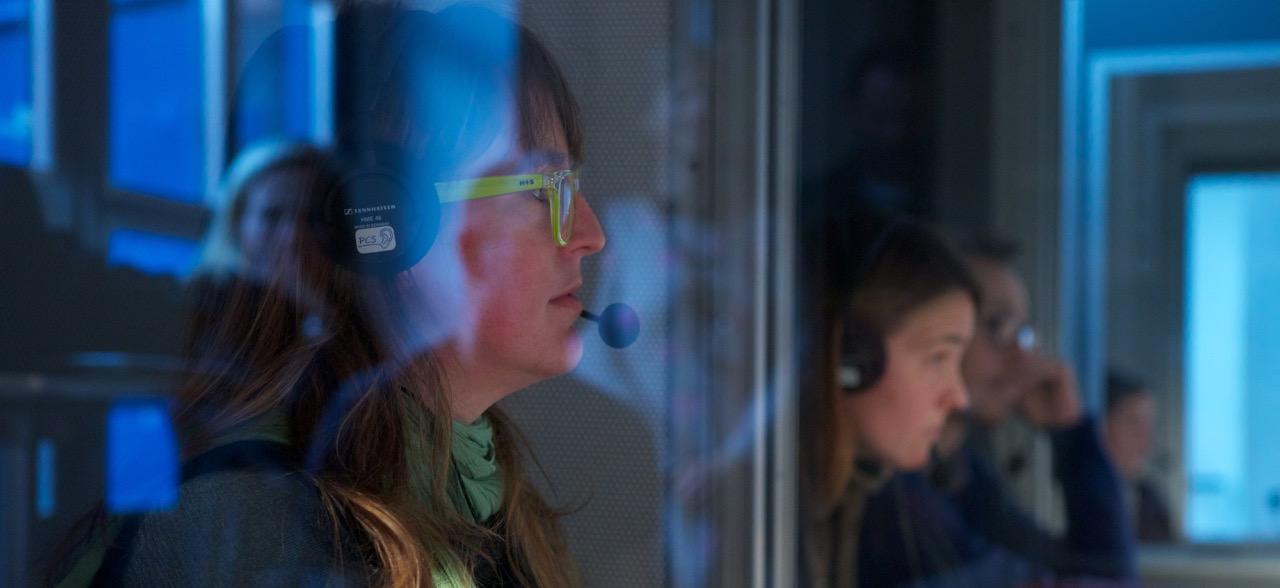 Eine Dolmetscherin für Leichte Sprache sitzt in der Dolmetscherkabine. Sie trägt Kopfhörer und ein Mikrofon.